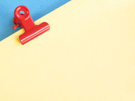 Red paper clip holding pile of yellow pages on blue background photo