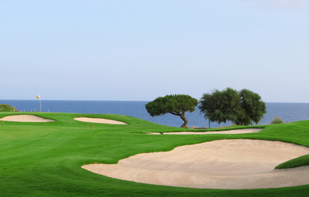 Green of a golf field with a beautiful view to the sea Stock Photo