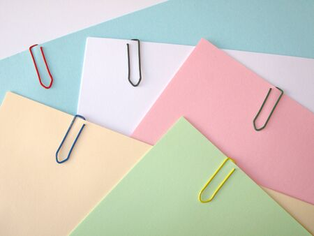 Stack of pastel papers attached with  paper clips photo