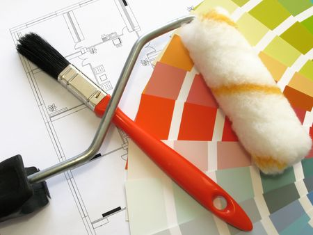 Color samples for selection and a roll and a painter�s brush with house plan on background photo