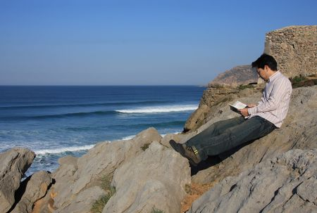 educating: Young man reading a book on a rock with a great view over the sea