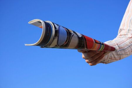 mag: Hand holding a magazine roll isolated on a blue sky