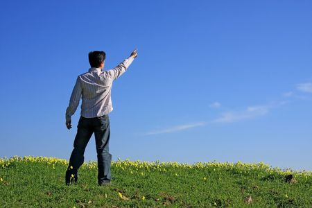 green back: Young man pointing with his finger to the blue sky