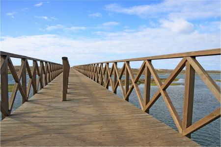 Wooden footbridge over the water near the beach photo