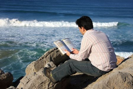 Young man reading a book on a rock with a great view over the sea photo