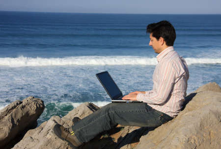 Young man working with a laptop enjoying a beautiful seascape photo