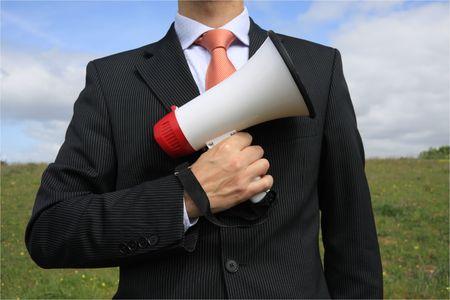 Businessman with a black suit holding a megaphone like gun photo