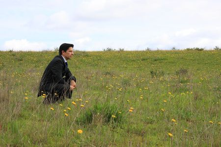 A young businessman sitting in a field thinking about a solution photo