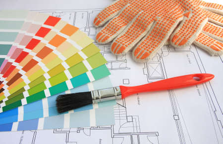 A color guide, a brush and gloves with a house plan on background photo
