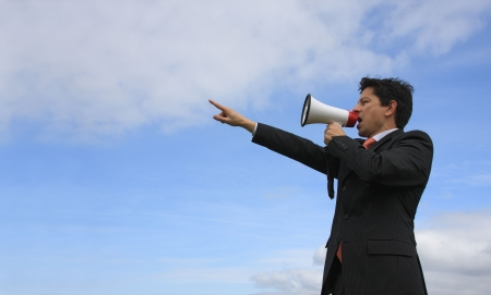 A business man giving an order with a megaphone with a blue sky as Background photo