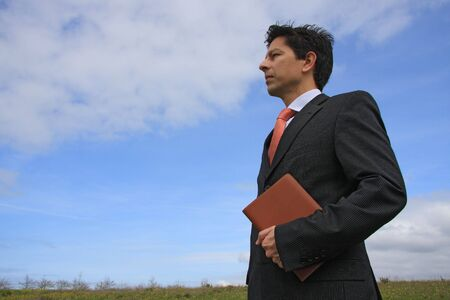 Young business man holding a executive notebook ready to work on the nature photo