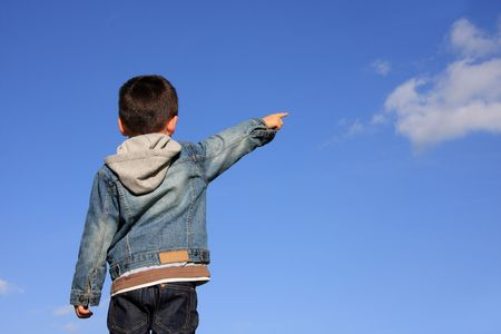 kid pointing: Young boy pointing with his finger to the blue sky