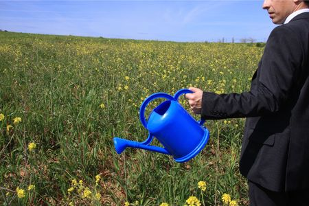 Detail of a business man with a blue watering can in a field  photo