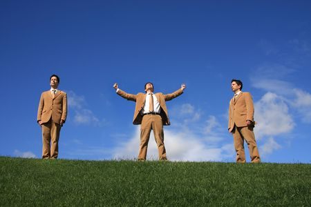 Three business men with diferent posture at the top of a hill photo