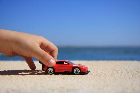 carritos de juguete: Primer plano de un ni�o mano jugando con un coche de carreras  Foto de archivo