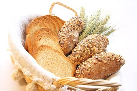 Assortment of baked bread with wheat isolated on white background photo