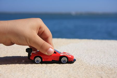 Close-up of a child hand playing with a red car