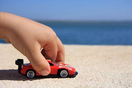 carritos de juguete: Primer plano de la mano de un ni�o jugando con un coche rojo