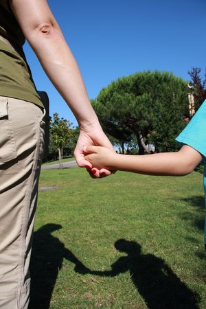 holding close: Mum holding the hand of her son on a park with shadow