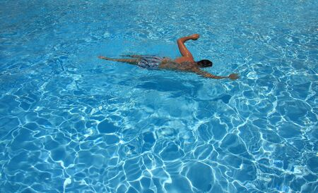 Young man swimming alone in a pool photo