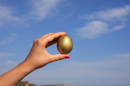 Female hand holding a golden egg Stock Photo - 3505314