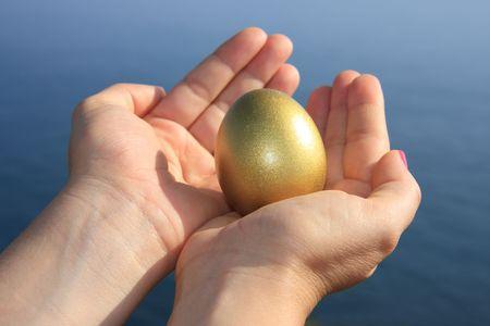 Female hand holding a golden egg Stock Photo - 3505316
