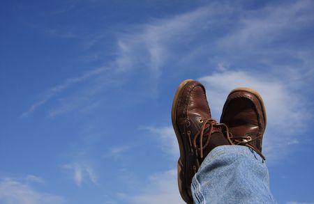 Man with his feet crossed enjoying a beautiful blue sky photo