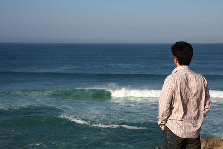 Back view of an young man looking to te sea  photo
