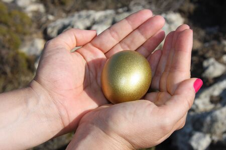 Woman hand holding a golden egg symbolizing success Stock Photo - 3616537