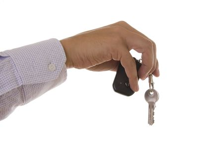 Detail of a hand holding a house key with a alarm remote control photo