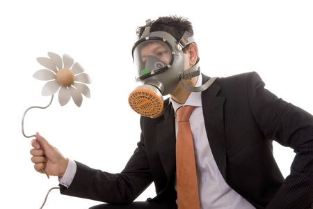 A businessman with a gas mask looking to an artificial flower photo