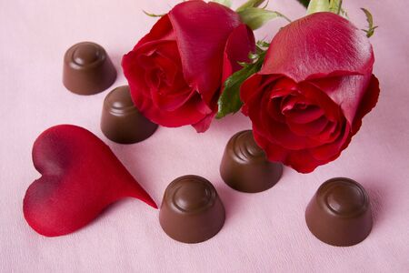 Two beautiful red roses with chocolates on a pink background photo