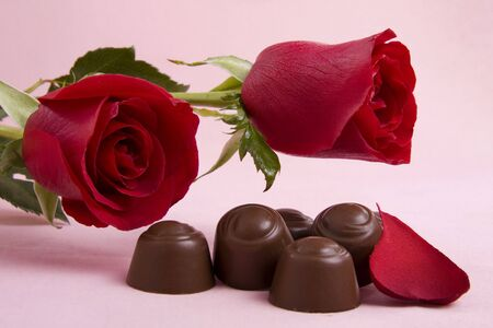 Two red roses with chocolates on a pink background