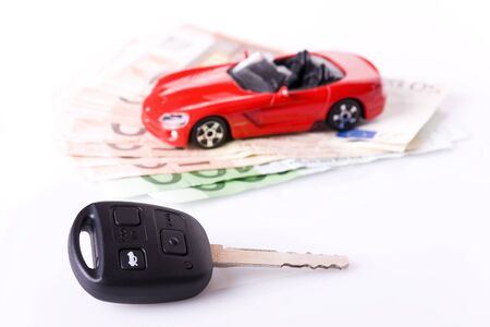 personal finance: New car Concept - Key and a red car with euro banknotes (selective focus on the key)