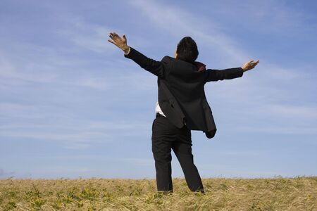 with raised: A successful business man with his arm outstretched on a field