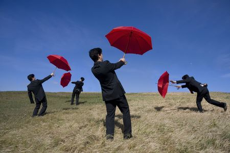 Four businessman with red umbrellas on the nature photo