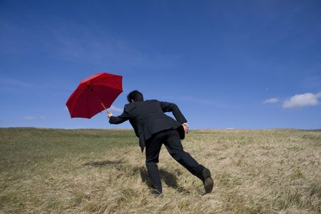 Business man with an open umbrella on the meadow photo