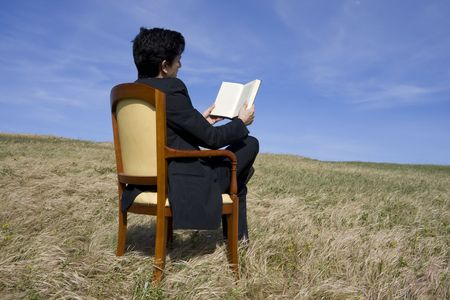 Business man reading a book on the meadow  photo