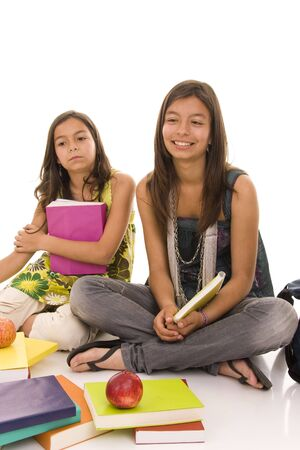 Two sisters doing shool homework isolated in white
