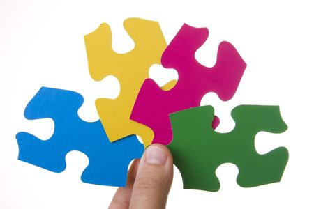 Hand holding a four colorful puzzles isolated on white photo