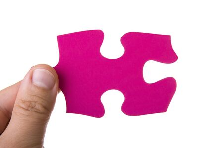 Hand holding a pink puzzle isolated on white photo