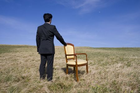 Men with an armchair looking to the horizon photo