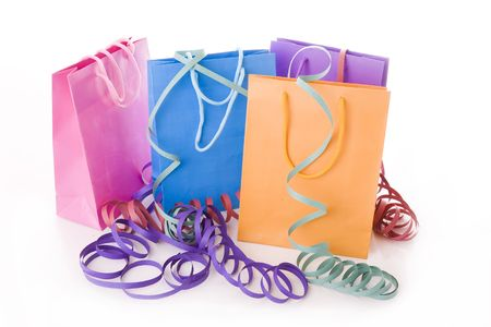 Colorful shopping bags with party ribbons isolated on white photo