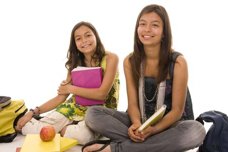 Two young girls doing school homework isolated on white photo
