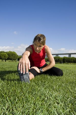 Woman stretching her leg on the park photo
