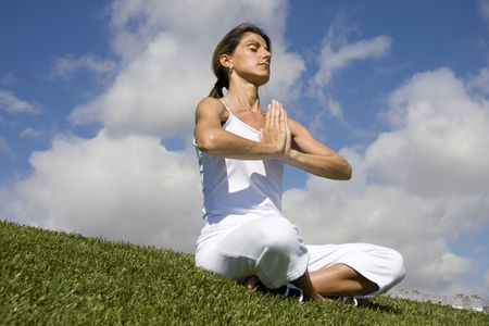 Pretty woman in white doing yoga outdoor photo