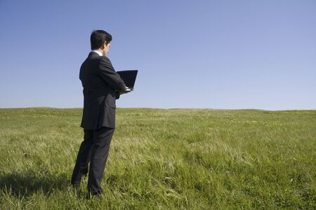 Young business man with a laptop on a green field photo