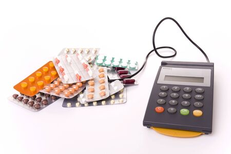 pos: Health cost concept - POS Terminal with a lot of pill tablets (focus on the POS) Stock Photo