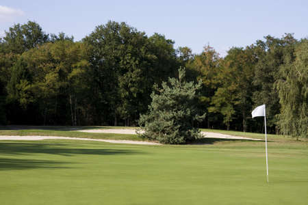 View of a golf course - Green with a white flag photo