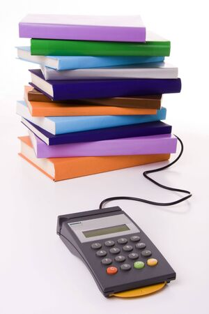 pos: Education cost concept - POS terminal with a stack of colorful books (focus on the POS)